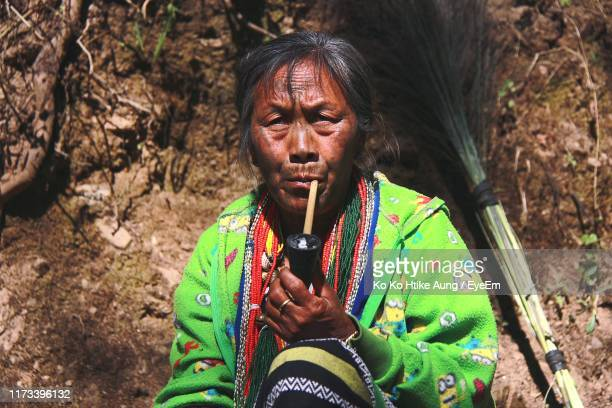 portrait of woman smoking pipe while sitting outdoors - ko ko htike aung stock pictures, royalty-free photos & images