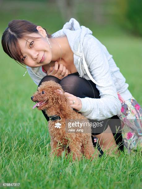 Portrait of woman squatting down to pet poodle