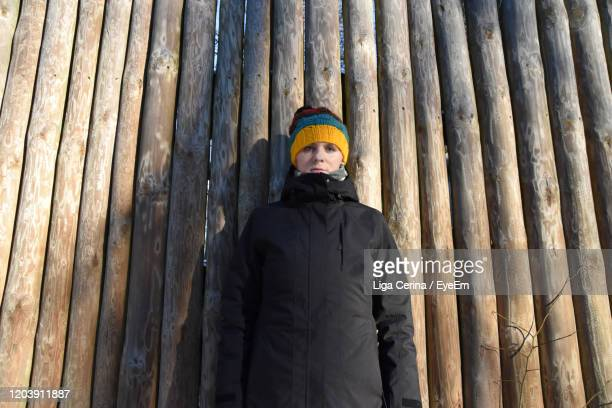 portrait of woman standing against bamboo fence - liga cerina stock pictures, royalty-free photos & images