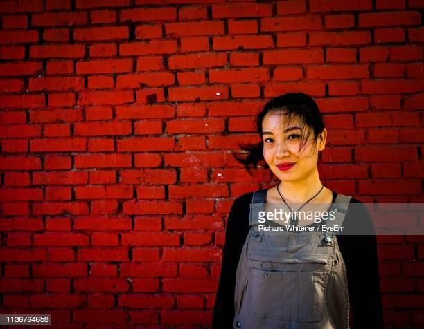 portrait of woman standing against brick wall - henan province stock photos and pictures