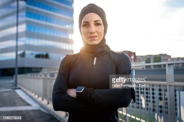 portrait of woman standing against building in city - united arab emirates stock pictures, royalty-free photos & images