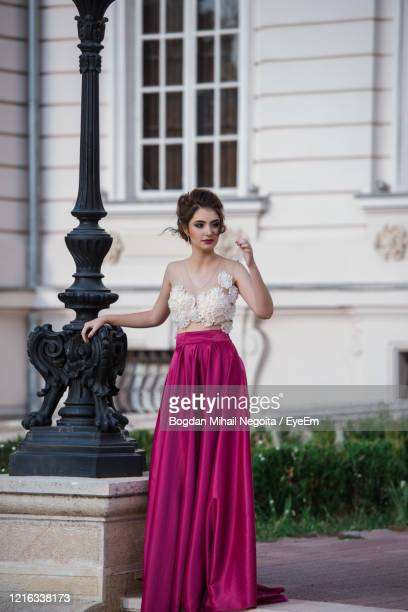 portrait of woman standing against building - evening gown stock pictures, royalty-free photos & images