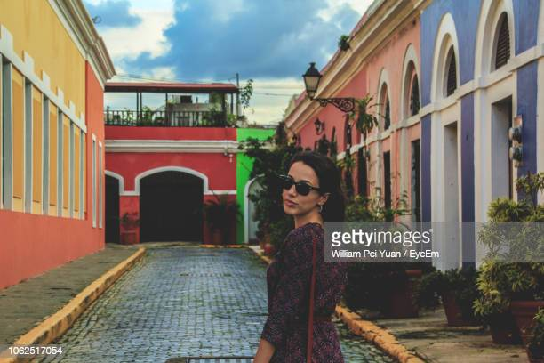 portrait of woman standing against buildings in city - san juan stock pictures, royalty-free photos & images