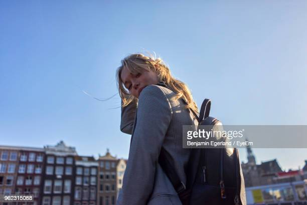Portrait Of Woman Standing Against Clear Sky In City