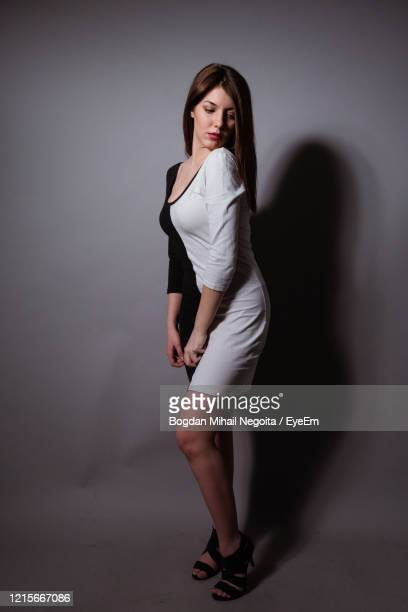 portrait of woman standing against gray background - bogdan negoita stock pictures, royalty-free photos & images