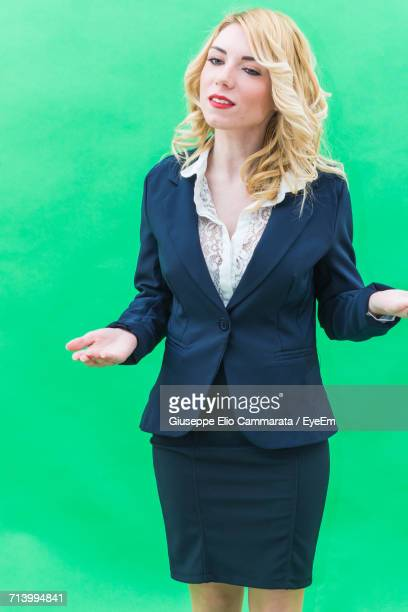 portrait of woman standing against green wall - cammarata stock photos and pictures