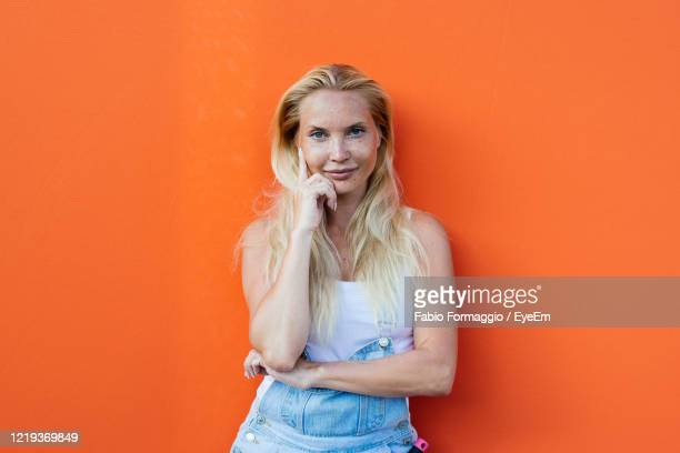 portrait of woman standing against orange background - orange background stock pictures, royalty-free photos & images