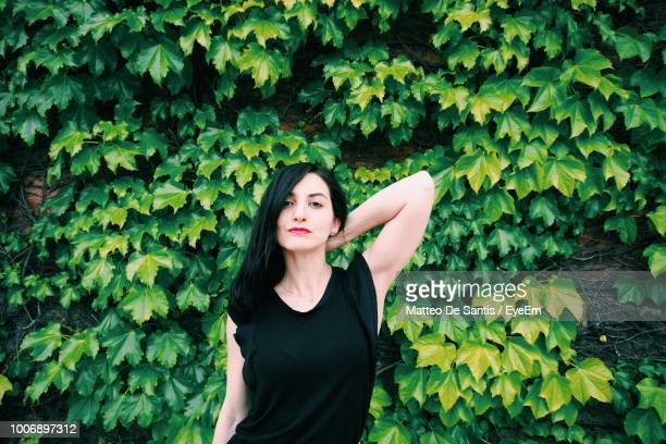 portrait of woman standing against plants - sleeveless dress - fotografias e filmes do acervo