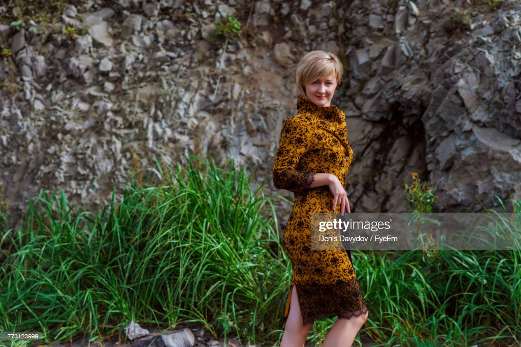 Portrait Of Woman Standing Against Rock Formations At Beach : Photo