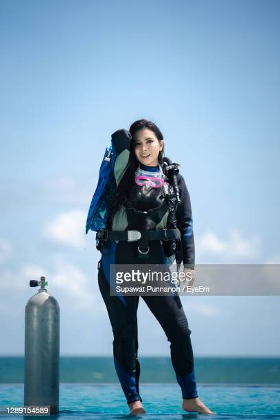 portrait of woman standing against sea and sky - aqualung diving equipment stock pictures, royalty-free photos & images