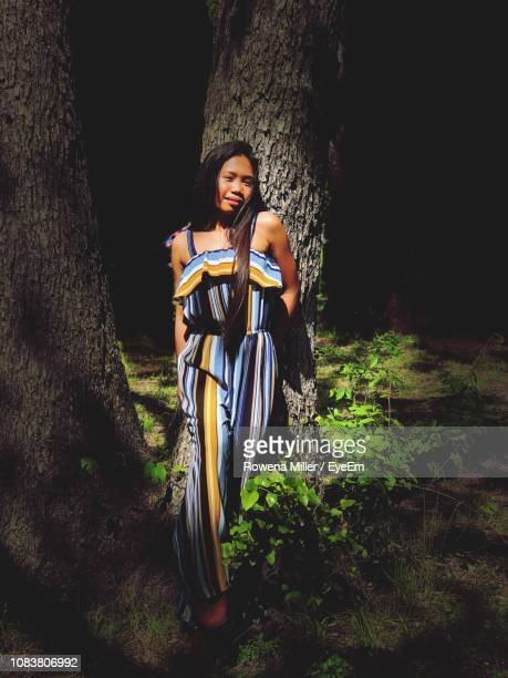 portrait of woman standing against tree trunk in forest - rowena miller stock photos and pictures