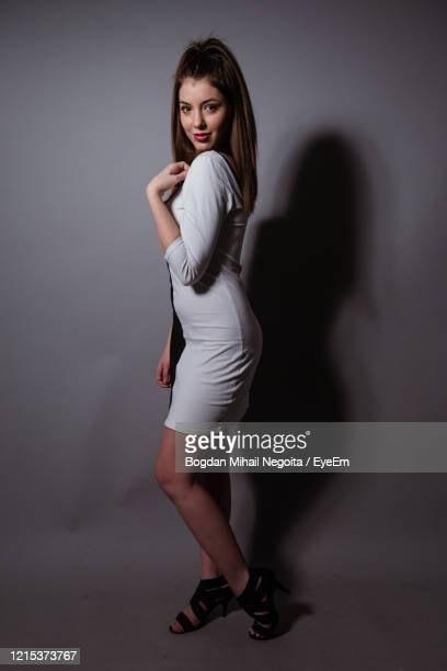portrait of woman standing against wall - bogdan negoita stock pictures, royalty-free photos & images