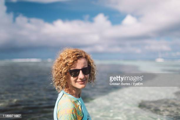 portrait of woman standing at beach - bortes stock photos and pictures