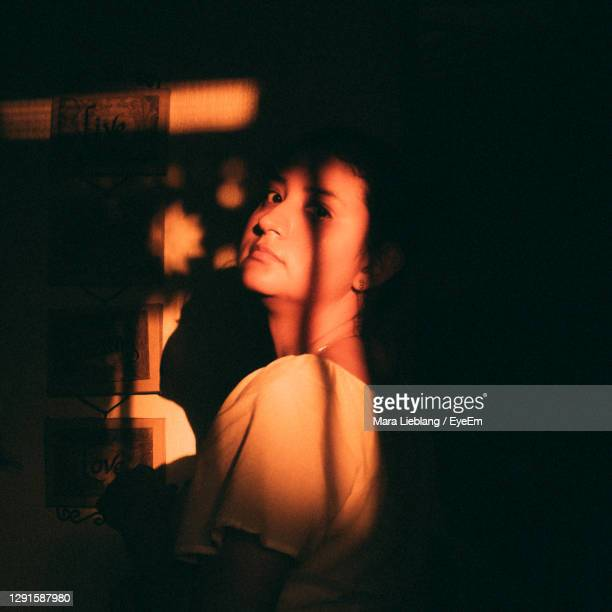 portrait of woman standing at home - golden hour stock pictures, royalty-free photos & images