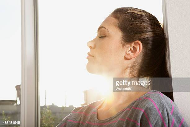 Portrait of woman standing at open window