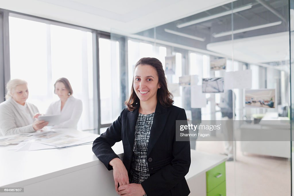 Portrait of woman standing at work desk in office : Foto de stock