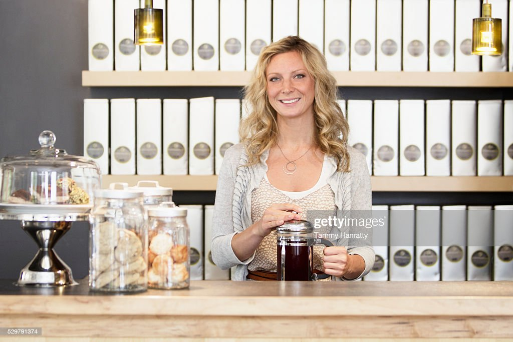 Portrait of woman standing behind counter : Stock Photo