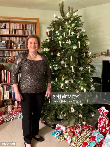 Portrait Of Woman Standing By Christmas Tree At Home