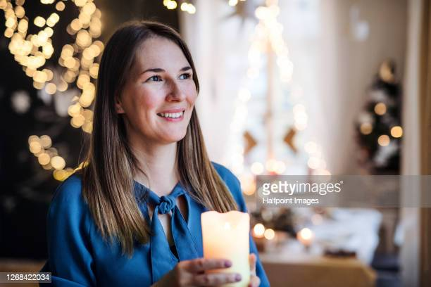 portrait of woman standing by christmas tree indoors at home, holding candle. - christmas decore candle stock pictures, royalty-free photos & images