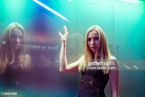 portrait of woman standing by illuminated wall - green dress stock pictures, royalty-free photos & images