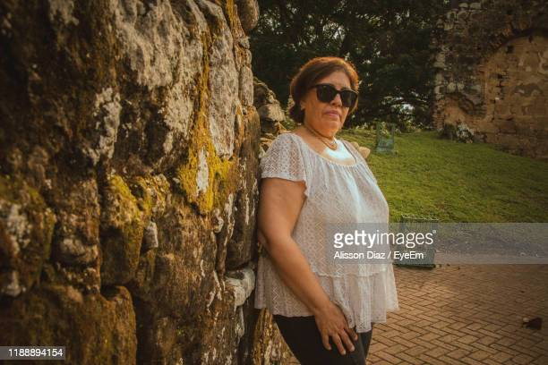portrait of woman standing by rock - alisson stock pictures, royalty-free photos & images