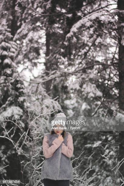 Portrait Of Woman Standing By Snow Covered Bare Trees
