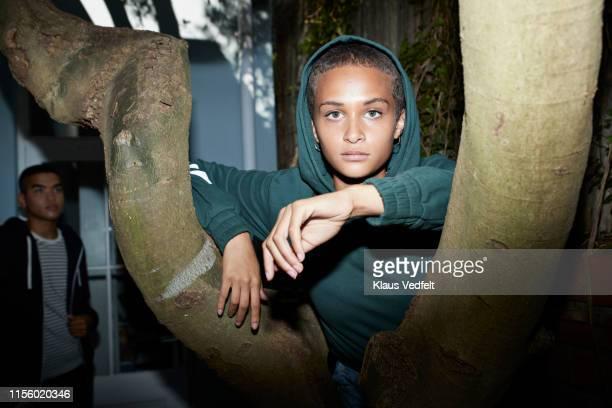 portrait of woman standing by tree - na moda descrição - fotografias e filmes do acervo
