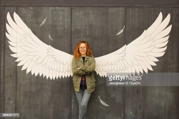 Portrait Of Woman Standing By Wall With Wings