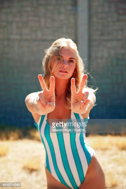 Portrait Of Woman Standing In Bikini Showing Peace Sign On Sunny Day