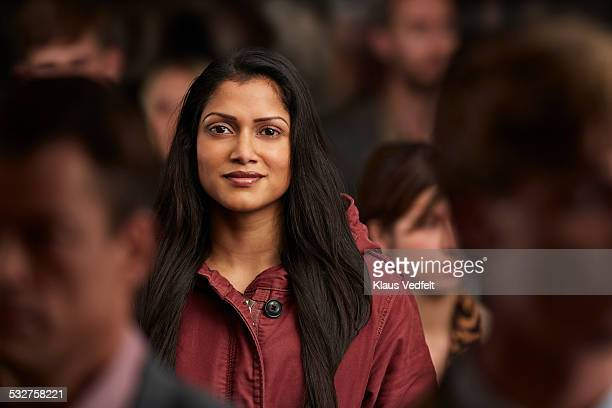 portrait of woman standing in crowd & smiling - indian subcontinent ethnicity stock pictures, royalty-free photos & images