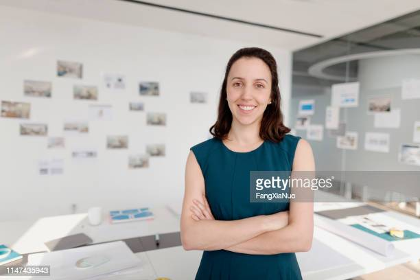 portrait of woman standing in design office - museum curator stock pictures, royalty-free photos & images