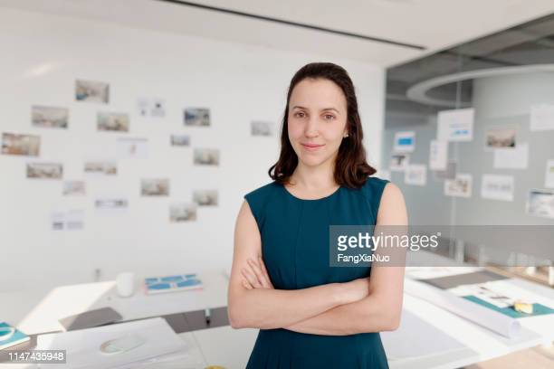 portrait of woman standing in design office with arms crossed - museum curator stock pictures, royalty-free photos & images