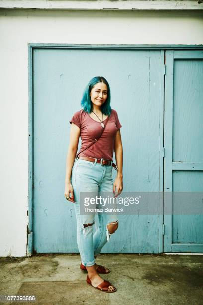 portrait of woman standing in front of blue wall - hair colour stock pictures, royalty-free photos & images