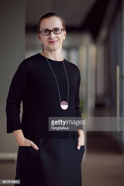portrait of woman standing in office - paardenstaart haar naar achteren stockfoto's en -beelden