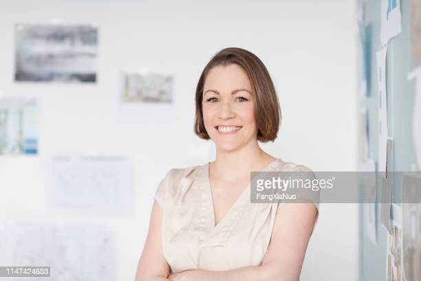 portrait of woman standing in office with diagrams on wall - museum curator stock pictures, royalty-free photos & images
