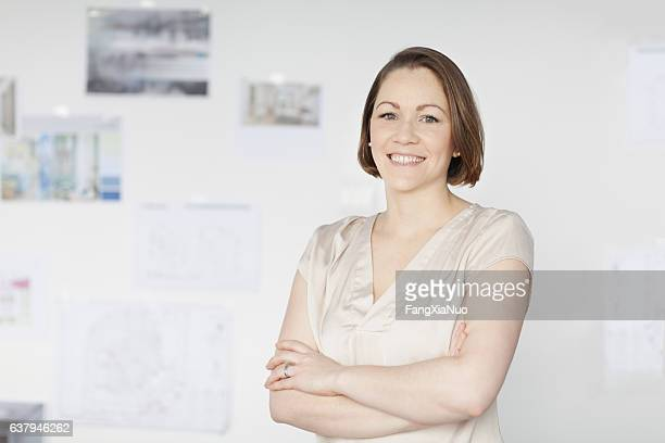Portrait of woman standing in office with diagrams on wall