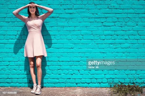 色の壁の横に立っている女性の肖像画。