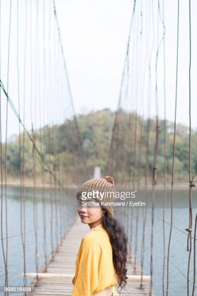 Portrait Of Woman Standing On Bridge Over River Against Sky