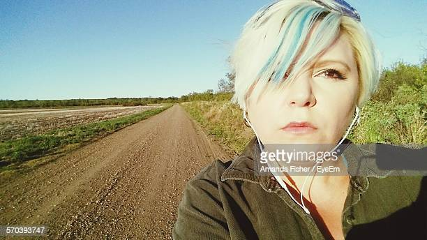 Portrait Of Woman Standing On Dirt Road Against Clear Sky