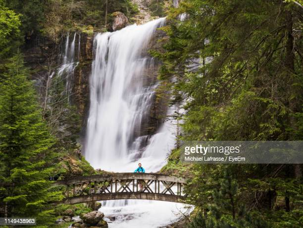 portrait of woman standing on footbridge against waterfall in forest - イゼール県 ストックフォトと画像