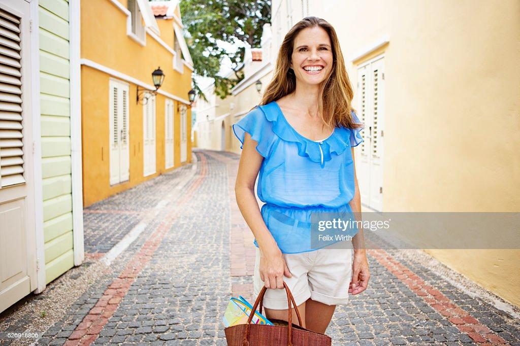 Portrait of woman standing on narrow street : ストックフォト
