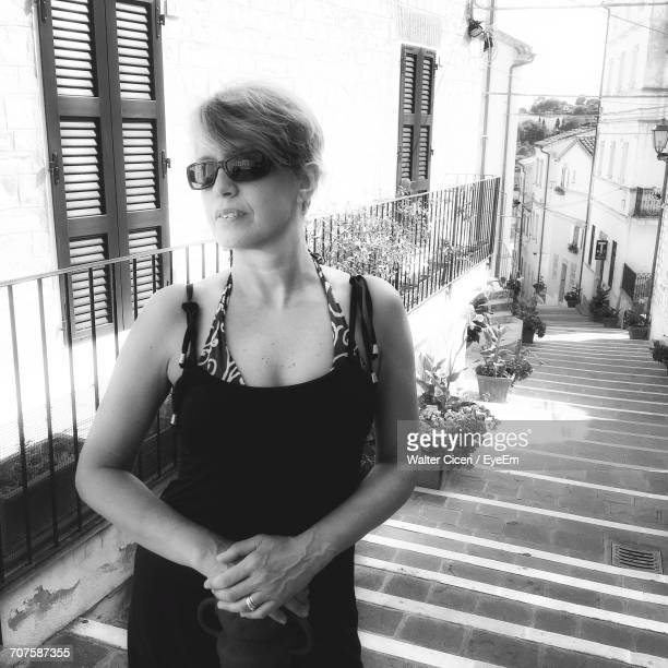 portrait of woman standing on steps by building in city - walter ciceri foto e immagini stock