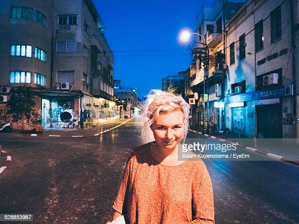 portrait of woman standing on street in tel aviv at night - israeli woman stock pictures, royalty-free photos & images