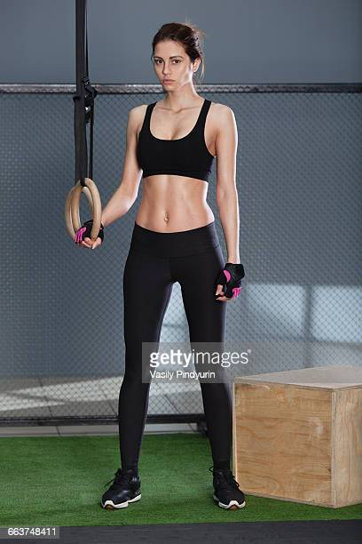 Portrait of woman standing with gymnastic rings against fence