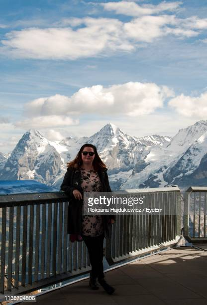 Portrait Of Woman Standing With Snowcapped Mountain In Background Against Cloudy Sky