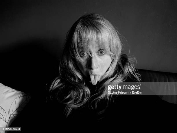 portrait of woman sticking out tongue at home - sabine kriesch stock-fotos und bilder