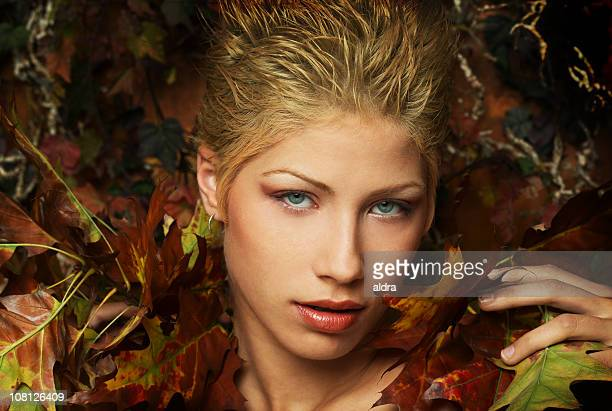portrait of woman surrounded by autumn leaves - fine art portrait stock photos and pictures