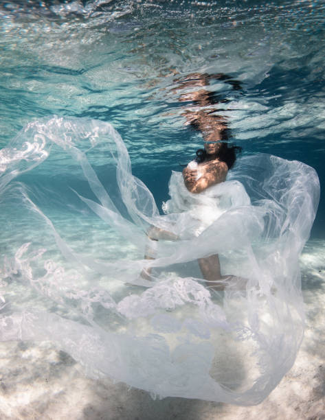 Portrait of woman swimming underwater in white dress,Bora Bora,French Polynesia