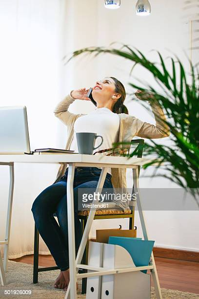 Portrait of woman telephoning with smartphone at modern home office