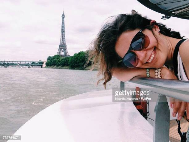 Portrait Of Woman Traveling In Boat Against Eiffel Tower